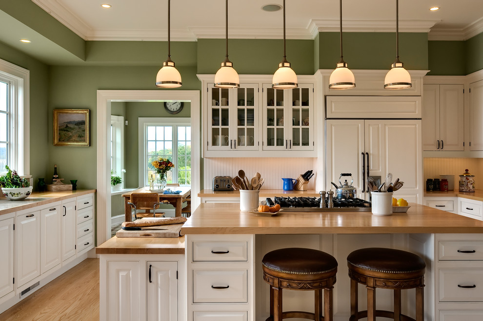 Elegant eat-in kitchen photo in New York with beaded inset cabinets, wood countertops, paneled appliances, white cabinets, an undermount sink and white backsplash