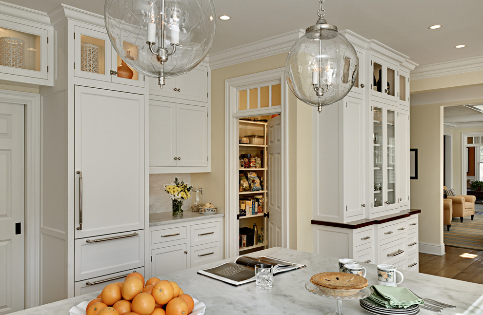 Elegant eat-in kitchen photo in New York with marble countertops, shaker cabinets, white cabinets, a farmhouse sink, white backsplash and paneled appliances