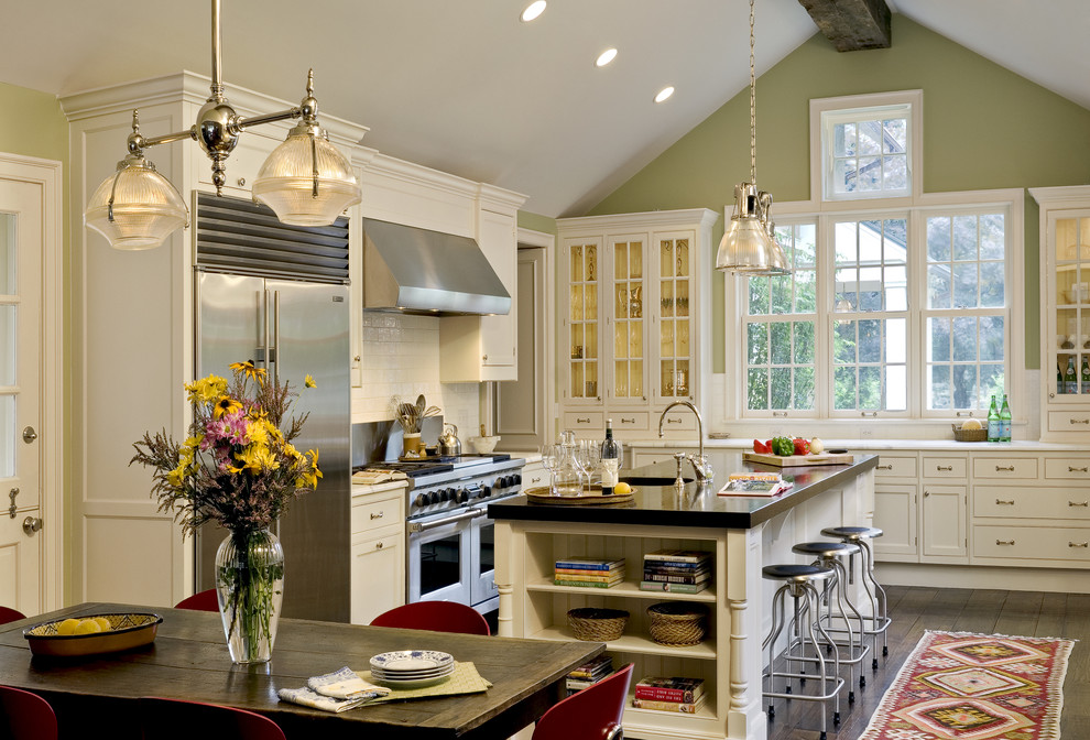 Example of a classic eat-in kitchen design in New York with beaded inset cabinets, white cabinets, stainless steel appliances, white backsplash, glass tile backsplash and marble countertops