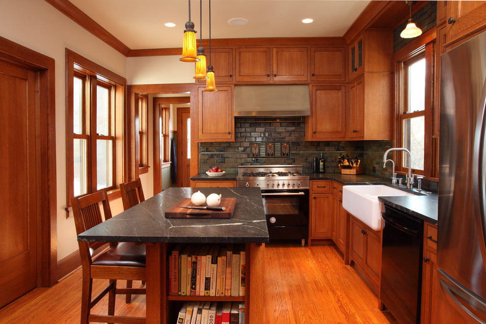 Example of an arts and crafts l-shaped enclosed kitchen design in Minneapolis with a farmhouse sink, recessed-panel cabinets, medium tone wood cabinets, soapstone countertops and stainless steel appliances