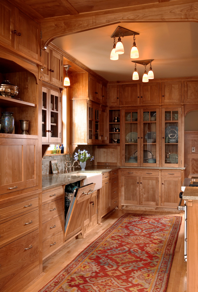 Inspiration for a craftsman galley medium tone wood floor eat-in kitchen remodel in Minneapolis with a farmhouse sink, medium tone wood cabinets, recessed-panel cabinets, paneled appliances, gray backsplash, no island, granite countertops and stone tile backsplash