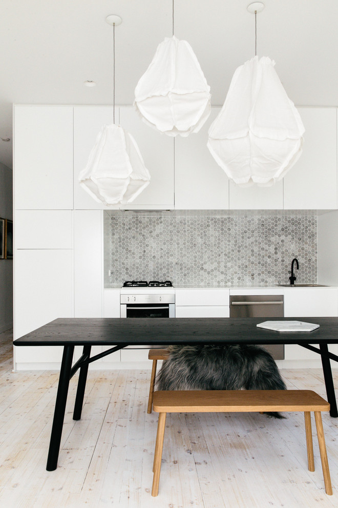 Inspiration for a scandinavian single-wall light wood floor eat-in kitchen remodel in Sydney with gray backsplash, stone tile backsplash, stainless steel appliances, flat-panel cabinets and white cabinets
