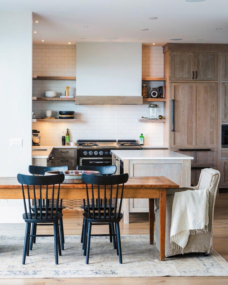 Example of a beach style l-shaped light wood floor eat-in kitchen design in Other with open cabinets, light wood cabinets, white backsplash, subway tile backsplash, black appliances and an island