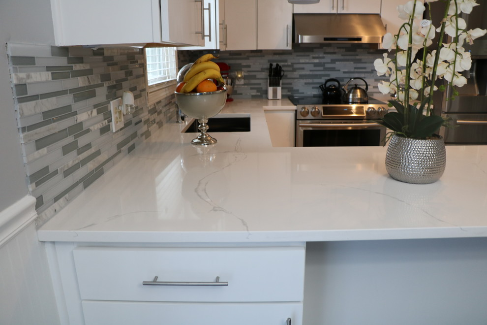Kitchen - small contemporary u-shaped porcelain tile and brown floor kitchen idea in Grand Rapids with an undermount sink, flat-panel cabinets, white cabinets, quartzite countertops, gray backsplash, matchstick tile backsplash, stainless steel appliances and a peninsula