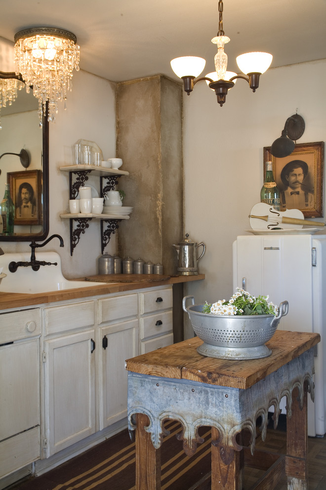 Example of a cottage chic kitchen design in Other with wood countertops, white cabinets, white appliances and a farmhouse sink