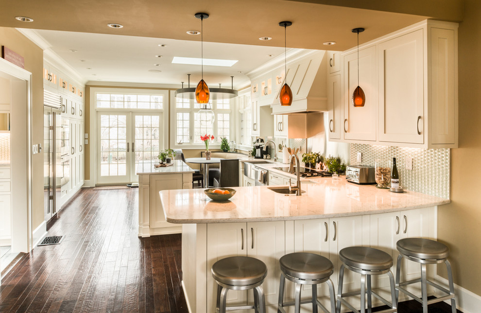 Example of a large transitional l-shaped medium tone wood floor eat-in kitchen design in Indianapolis with a farmhouse sink, shaker cabinets, white cabinets, quartz countertops, blue backsplash, mosaic tile backsplash, stainless steel appliances and a peninsula