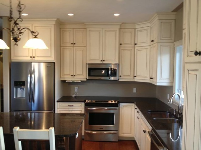 Example of a large classic l-shaped dark wood floor and brown floor enclosed kitchen design in Toronto with a double-bowl sink, raised-panel cabinets, white cabinets, quartz countertops, stainless steel appliances and an island