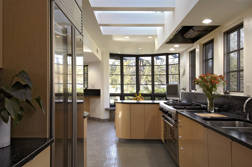 Example of a trendy galley enclosed kitchen design in Boston with stainless steel appliances, a double-bowl sink, flat-panel cabinets and light wood cabinets