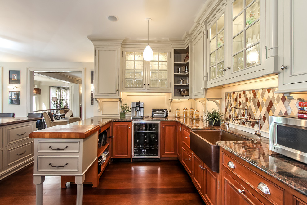 Example of a large transitional l-shaped limestone floor eat-in kitchen design in New York with a farmhouse sink, raised-panel cabinets, medium tone wood cabinets, wood countertops, multicolored backsplash, stone tile backsplash, paneled appliances and two islands