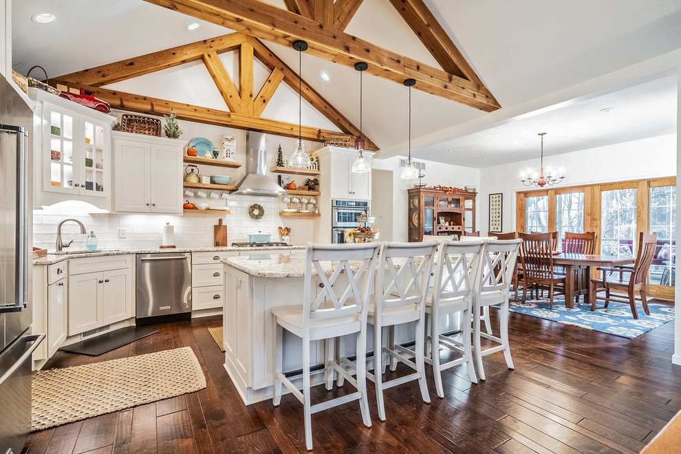 Inspiration for a large country l-shaped medium tone wood floor eat-in kitchen remodel in New York with an undermount sink, shaker cabinets, white cabinets, quartz countertops, white backsplash, subway tile backsplash, stainless steel appliances and an island