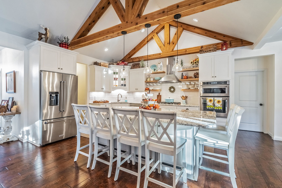Eat-in kitchen - large country l-shaped medium tone wood floor eat-in kitchen idea in New York with an undermount sink, shaker cabinets, white cabinets, quartz countertops, white backsplash, subway tile backsplash, stainless steel appliances and an island