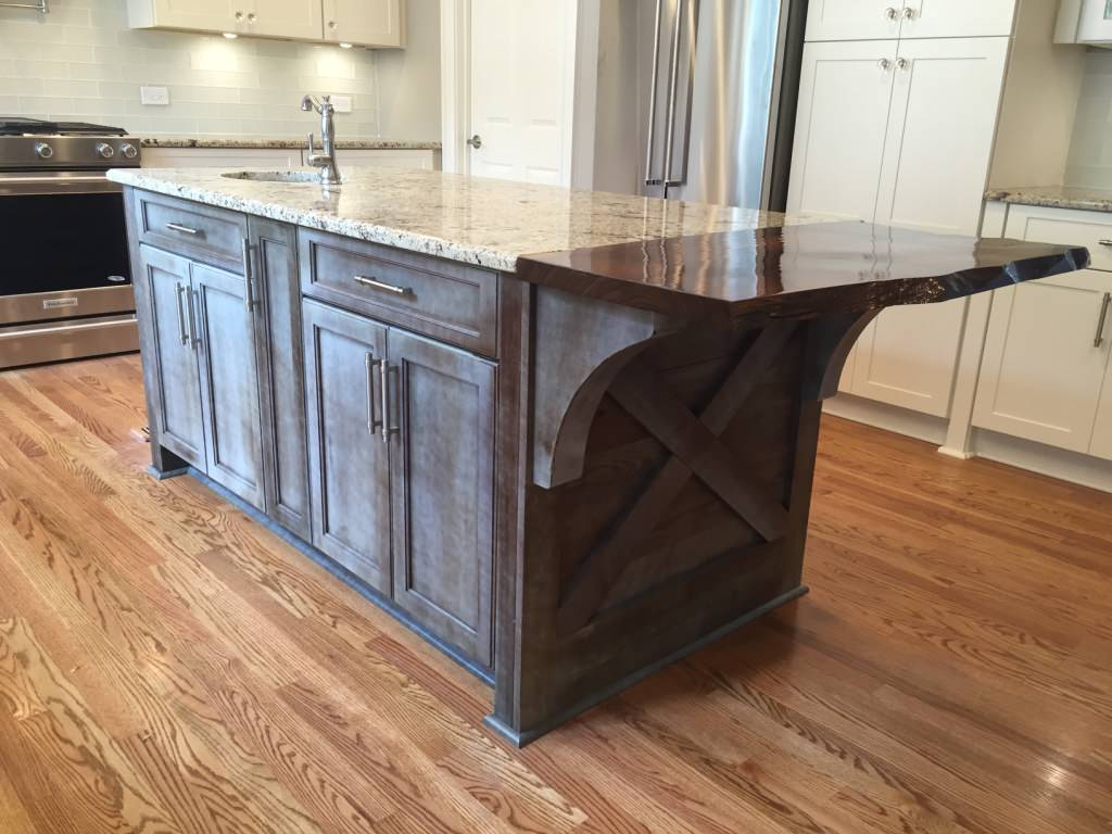"""Custom island with granite top and """"live edge"""" at seating area"""
