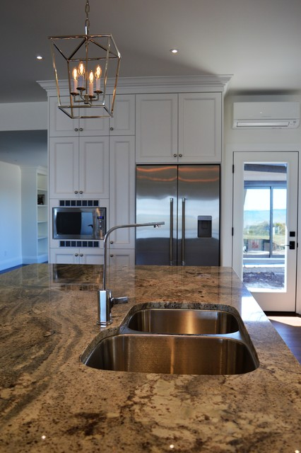 Eat-in kitchen - huge traditional l-shaped dark wood floor and brown floor eat-in kitchen idea in Toronto with an undermount sink, shaker cabinets, white cabinets, granite countertops, white backsplash, ceramic backsplash, stainless steel appliances, an island and multicolored countertops