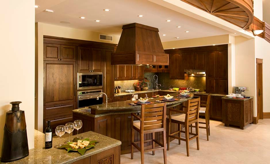 Inspiration for a mid-sized tropical u-shaped travertine floor and beige floor open concept kitchen remodel in Hawaii with raised-panel cabinets, medium tone wood cabinets, granite countertops, green backsplash, stone slab backsplash, paneled appliances, an island, green countertops and an undermount sink
