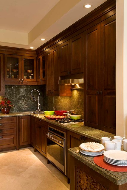 Inspiration for a mid-sized tropical u-shaped travertine floor and beige floor open concept kitchen remodel in Hawaii with an undermount sink, raised-panel cabinets, medium tone wood cabinets, granite countertops, green backsplash, stone slab backsplash, paneled appliances, an island and green countertops