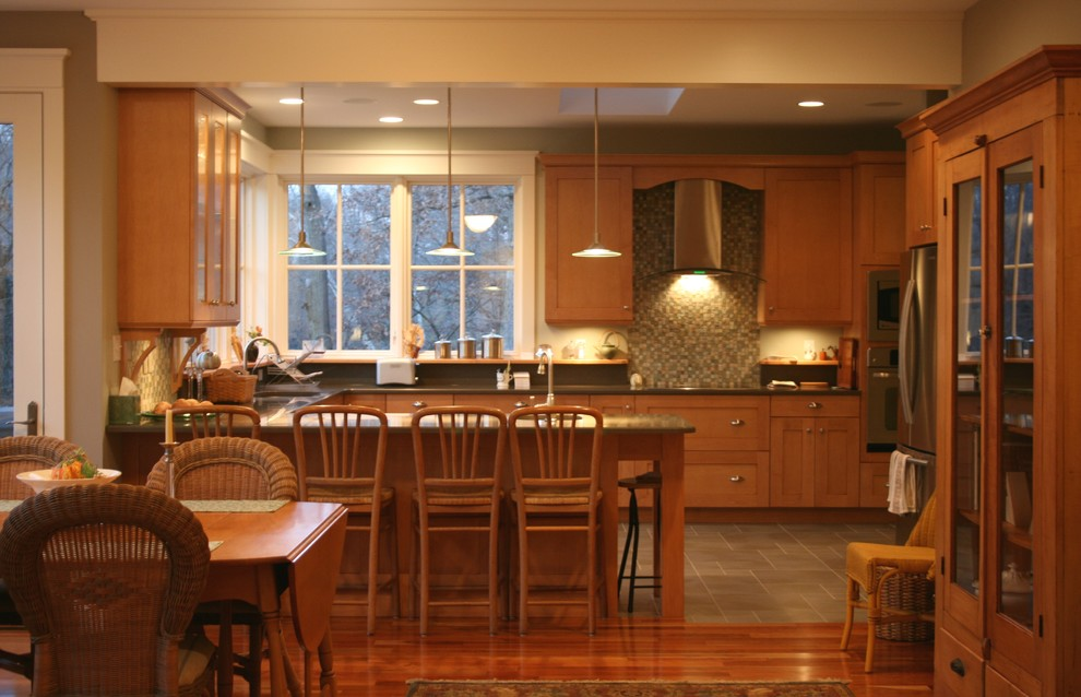 Eat-in kitchen - traditional u-shaped eat-in kitchen idea in Chicago with shaker cabinets, medium tone wood cabinets, multicolored backsplash and stainless steel appliances
