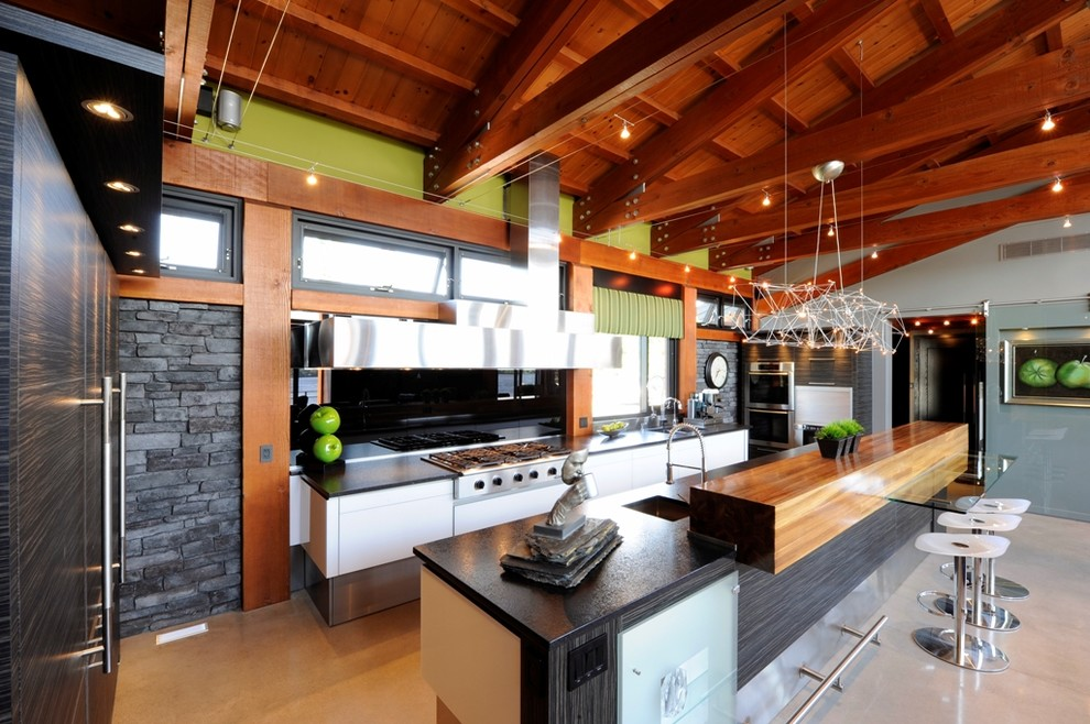 Eat-in kitchen - large contemporary l-shaped concrete floor eat-in kitchen idea in Ottawa with an integrated sink, flat-panel cabinets, dark wood cabinets, quartz countertops, metallic backsplash, mirror backsplash, white appliances and an island