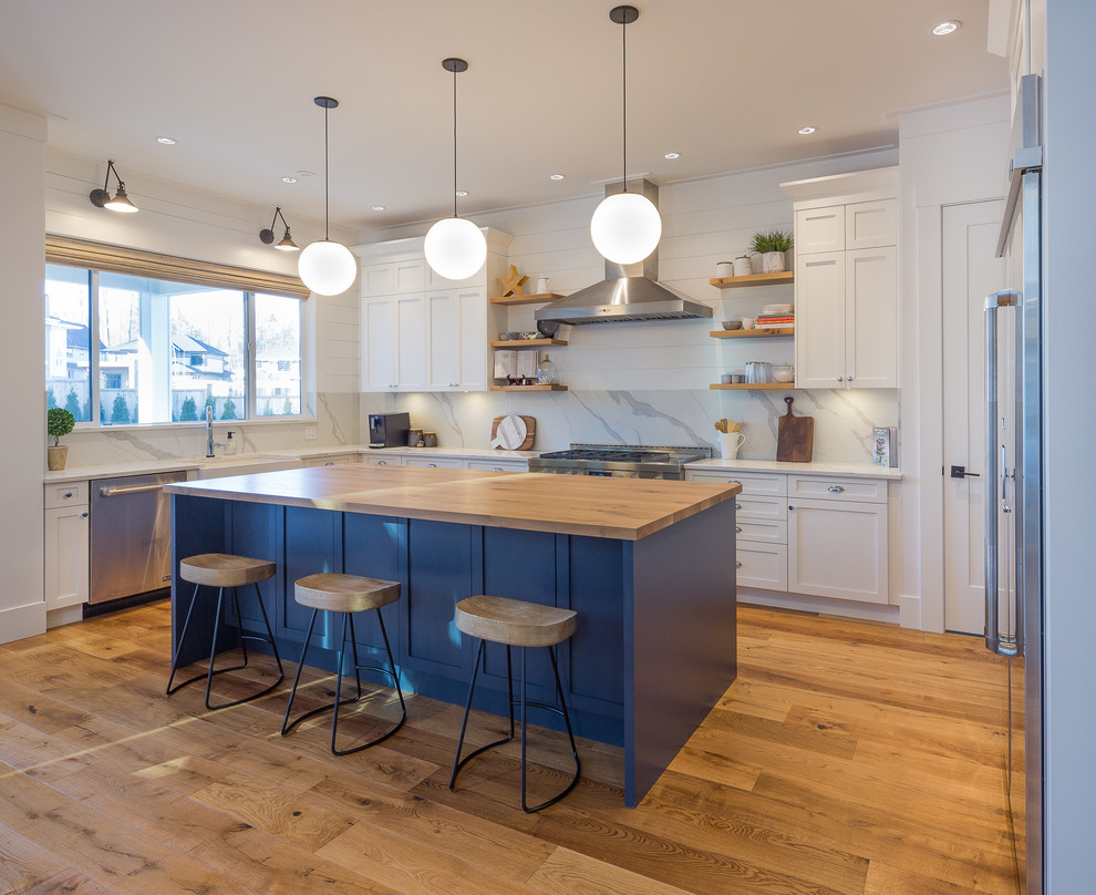 Inspiration for a transitional u-shaped medium tone wood floor and brown floor kitchen remodel in Vancouver with a farmhouse sink, shaker cabinets, white cabinets, wood countertops, stainless steel appliances, an island and brown countertops