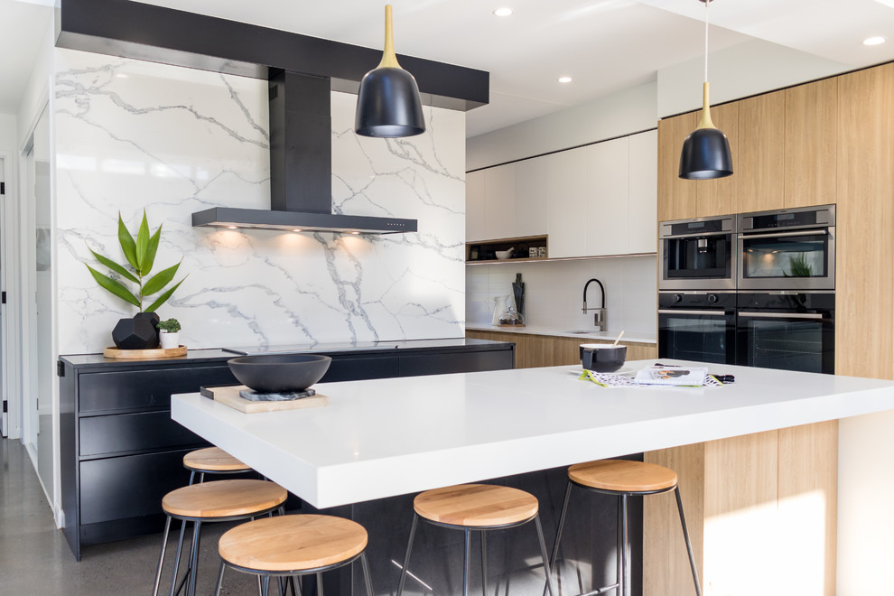 Kitchen - contemporary l-shaped gray floor kitchen idea in Sunshine Coast with flat-panel cabinets, light wood cabinets, white backsplash, stainless steel appliances and an island