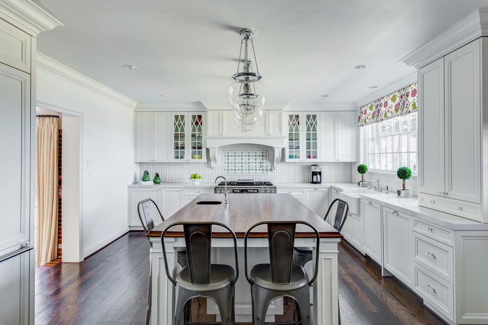 Inspiration for a large timeless l-shaped dark wood floor and brown floor kitchen remodel in Dallas with shaker cabinets, white cabinets, white backsplash and an island