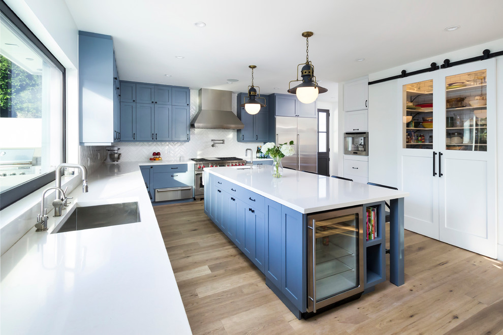 Example of a transitional l-shaped beige floor kitchen design in Los Angeles with an undermount sink, shaker cabinets, blue cabinets, white backsplash and stainless steel appliances