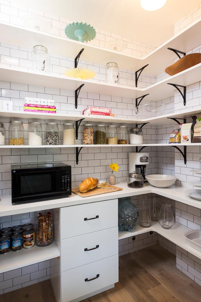 Transitional kitchen pantry photo in Los Angeles with white backsplash, subway tile backsplash and black appliances