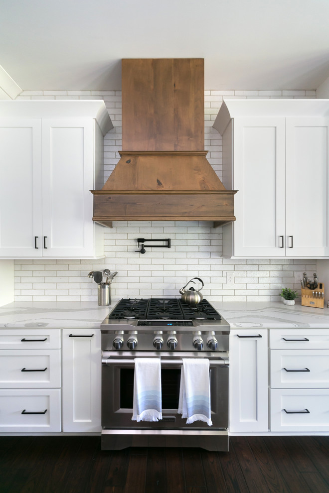 Huge cottage open concept kitchen photo in Charleston with a farmhouse sink, shaker cabinets, white cabinets, quartz countertops, white backsplash, brick backsplash, stainless steel appliances, an island and white countertops
