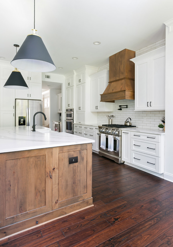 Inspiration for a huge country open concept kitchen remodel in Charleston with a farmhouse sink, shaker cabinets, white cabinets, quartz countertops, white backsplash, brick backsplash, stainless steel appliances, an island and white countertops