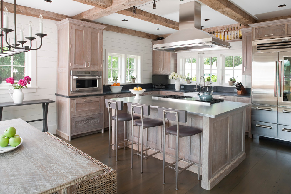 Inspiration for a large coastal l-shaped dark wood floor eat-in kitchen remodel in Bridgeport with a farmhouse sink, recessed-panel cabinets, distressed cabinets, stainless steel countertops, stainless steel appliances, gray backsplash and an island