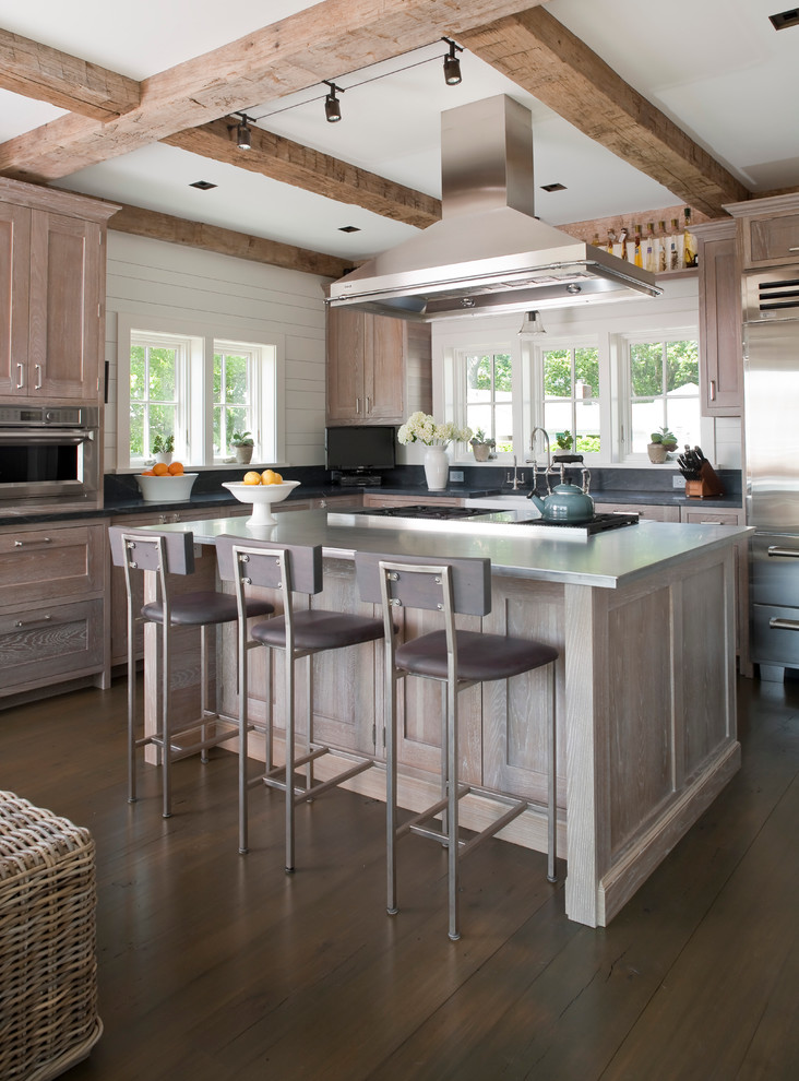 Inspiration for a large coastal l-shaped dark wood floor kitchen remodel in Bridgeport with stainless steel appliances, stainless steel countertops, recessed-panel cabinets, distressed cabinets, gray backsplash and an island