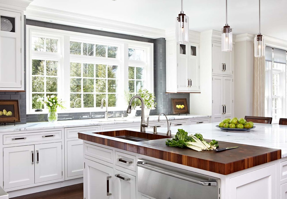 Kitchen - traditional kitchen idea in New York with an undermount sink, beaded inset cabinets, white cabinets, wood countertops, gray backsplash, subway tile backsplash, stainless steel appliances and an island