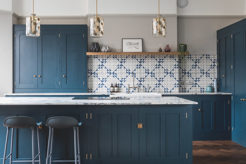 Inspiration for a large contemporary l-shaped dark wood floor and brown floor eat-in kitchen remodel in Other with a farmhouse sink, shaker cabinets, blue cabinets, marble countertops, blue backsplash, cement tile backsplash, stainless steel appliances and an island