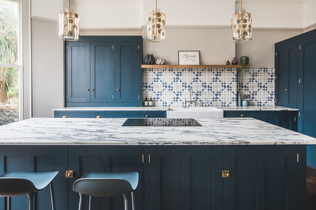 Design ideas for a large classic l-shaped kitchen/diner in Other with a belfast sink, shaker cabinets, blue cabinets, marble worktops, cement tile splashback, dark hardwood flooring, an island, brown floors, multi-coloured splashback and integrated appliances.