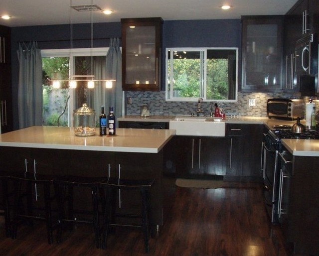 Dark wood cabinets, dark laminate wood flooring, white caesar stone counter tops