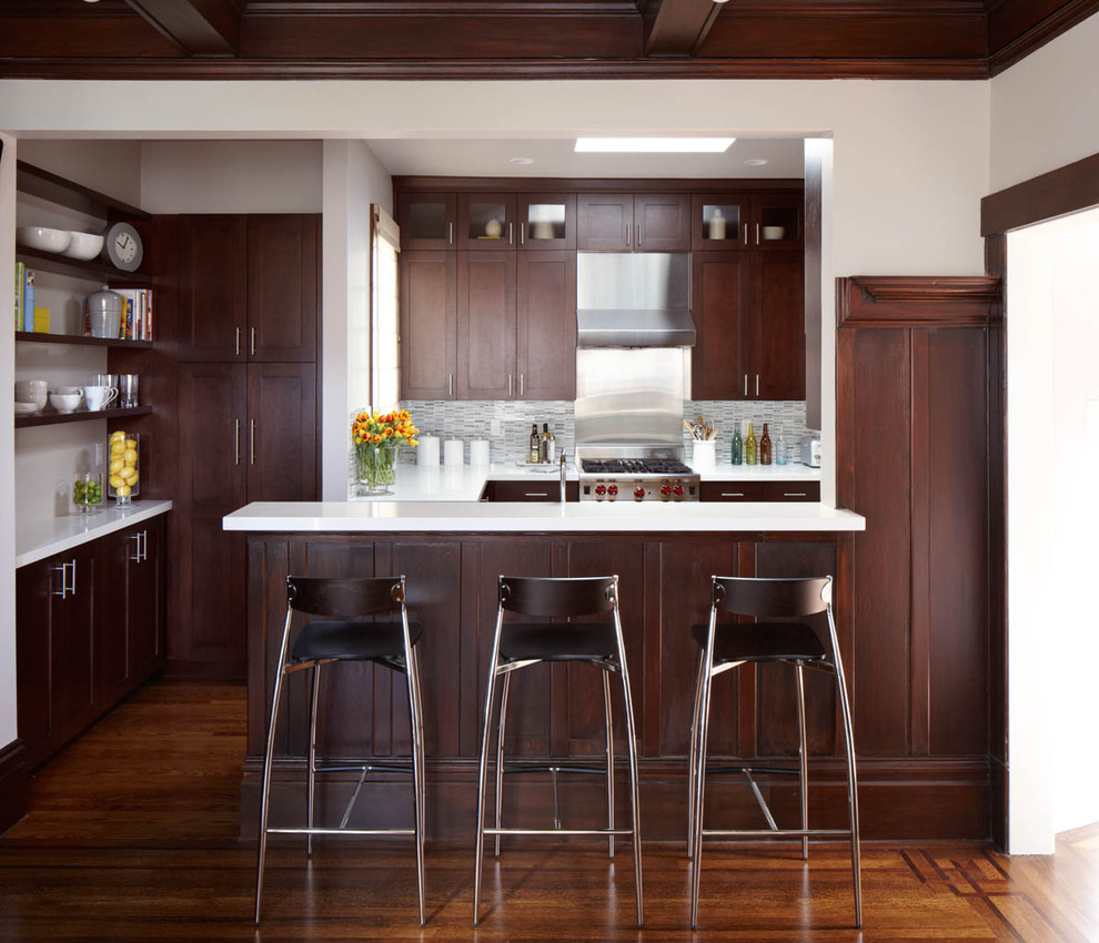 Inspiration for a contemporary galley kitchen remodel in San Francisco with shaker cabinets, dark wood cabinets, quartz countertops, gray backsplash and matchstick tile backsplash