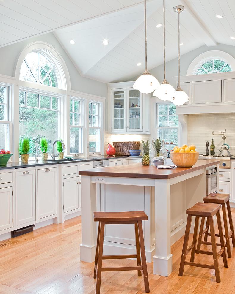 Elegant kitchen photo in Boston with beaded inset cabinets, wood countertops, white cabinets, white backsplash and subway tile backsplash