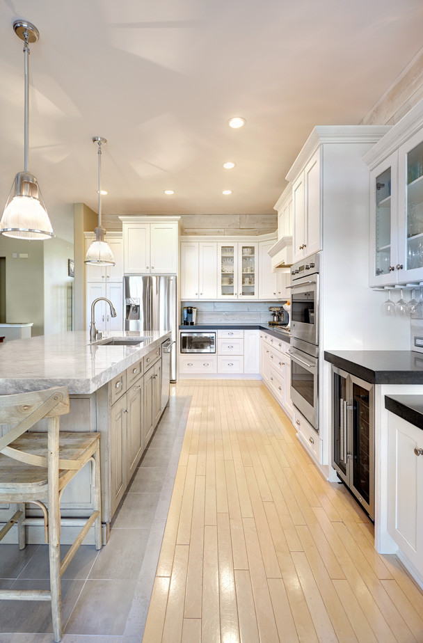 Open concept kitchen - mid-sized traditional l-shaped light wood floor open concept kitchen idea in Sacramento with an undermount sink, shaker cabinets, white cabinets, quartzite countertops, gray backsplash, mosaic tile backsplash, stainless steel appliances and an island