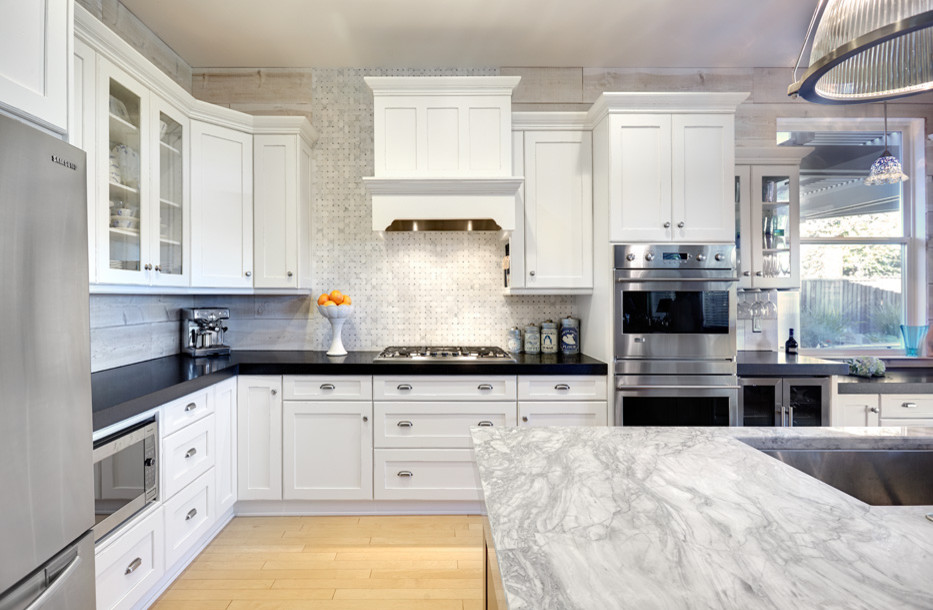 Inspiration for a mid-sized timeless l-shaped light wood floor eat-in kitchen remodel in Sacramento with an undermount sink, shaker cabinets, white cabinets, quartzite countertops, white backsplash, stainless steel appliances, mosaic tile backsplash and an island