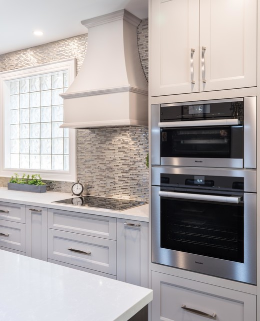 Example of a mid-sized transitional l-shaped porcelain floor and beige floor kitchen pantry design in Toronto with an undermount sink, shaker cabinets, gray cabinets, quartz countertops, white backsplash, mosaic tile backsplash, stainless steel appliances, an island and white countertops