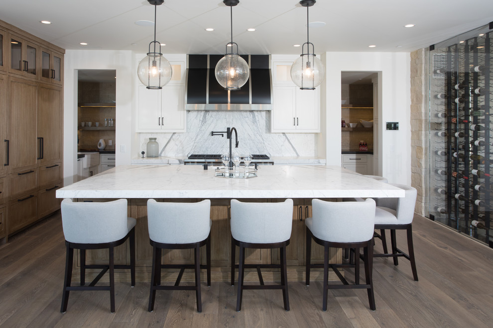 Inspiration for a coastal medium tone wood floor kitchen remodel in Orange County with shaker cabinets, white cabinets, white backsplash, stainless steel appliances and an island