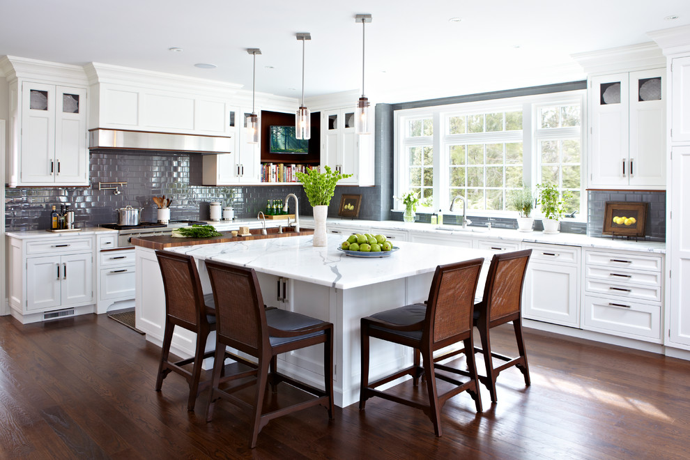 Example of a classic l-shaped dark wood floor kitchen design in New York with shaker cabinets, white cabinets, gray backsplash, ceramic backsplash and an island