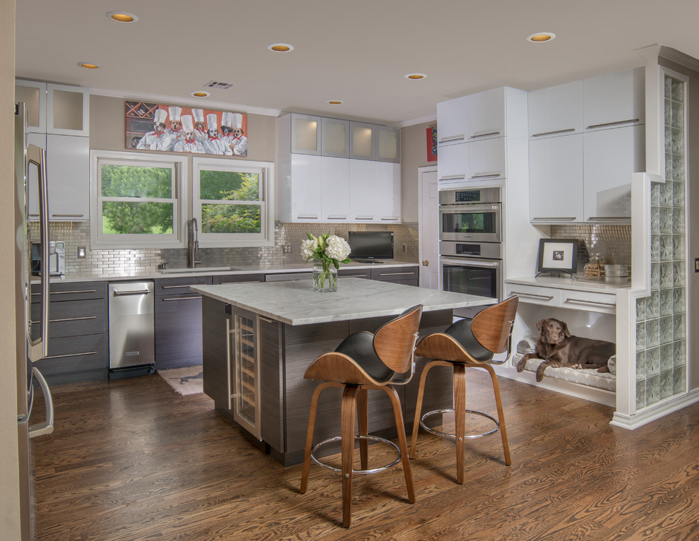 Example of a large trendy u-shaped dark wood floor and brown floor kitchen design in Other with an undermount sink, flat-panel cabinets, gray cabinets, metallic backsplash, stainless steel appliances, an island and subway tile backsplash