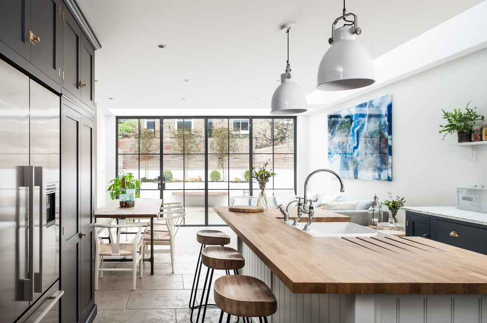 Inspiration for a large scandinavian galley kitchen/diner in London with a belfast sink, recessed-panel cabinets, wood worktops, stainless steel appliances, an island, black cabinets, white splashback and grey floors.