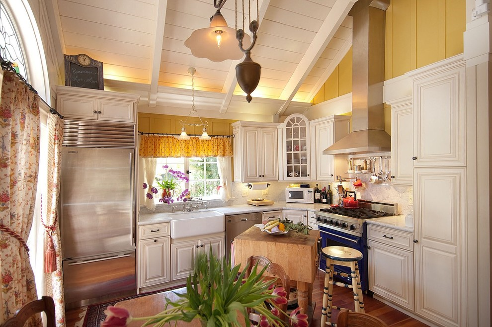 Example of a small classic l-shaped medium tone wood floor kitchen design in Seattle with colored appliances, a farmhouse sink, beaded inset cabinets, white cabinets, marble countertops, white backsplash, stone slab backsplash and an island