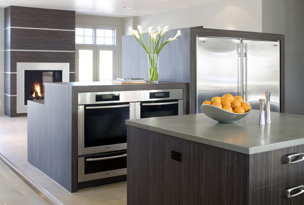 Example of a minimalist open concept kitchen design in Denver with stainless steel appliances, flat-panel cabinets and dark wood cabinets