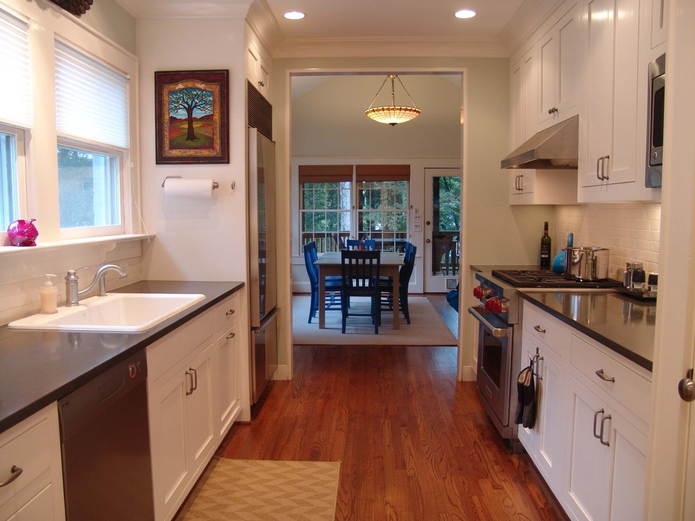 Example of a classic galley enclosed kitchen design in Atlanta with stainless steel appliances, a drop-in sink, shaker cabinets, white cabinets, white backsplash and subway tile backsplash