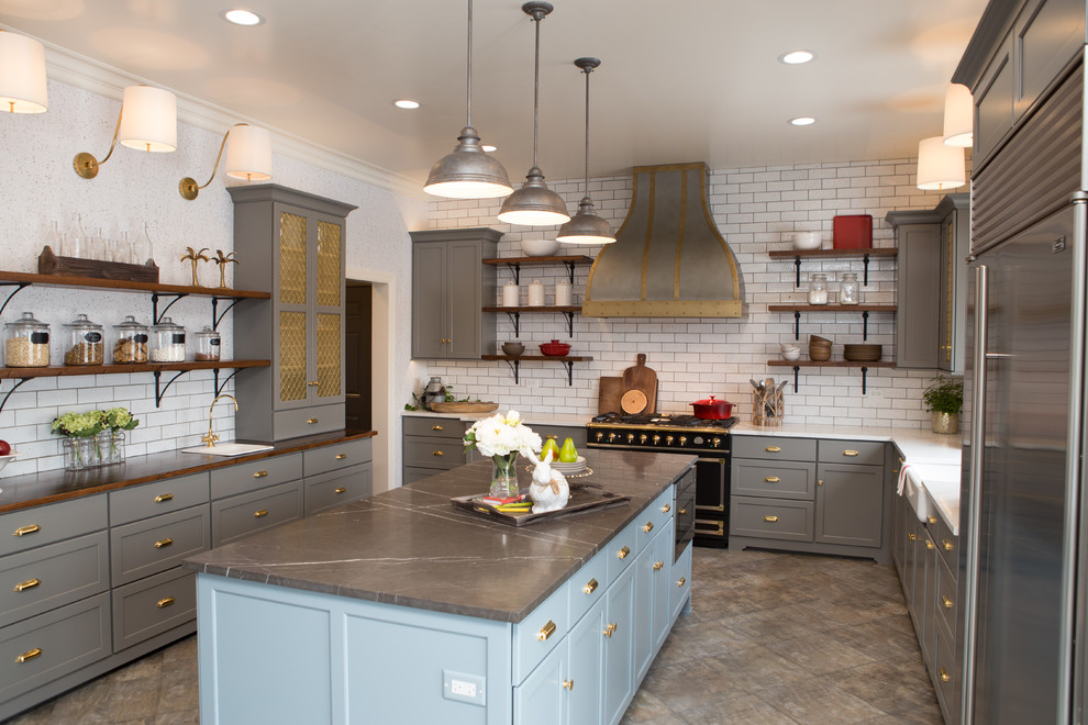 Enclosed kitchen - large transitional porcelain tile and gray floor enclosed kitchen idea in Chicago with a farmhouse sink, shaker cabinets, gray cabinets, limestone countertops, white backsplash, subway tile backsplash, black appliances, an island and gray countertops