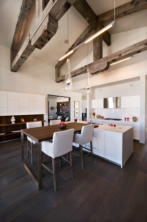 Big and open modern kitchen featuring a wood and metal pub table and four stools