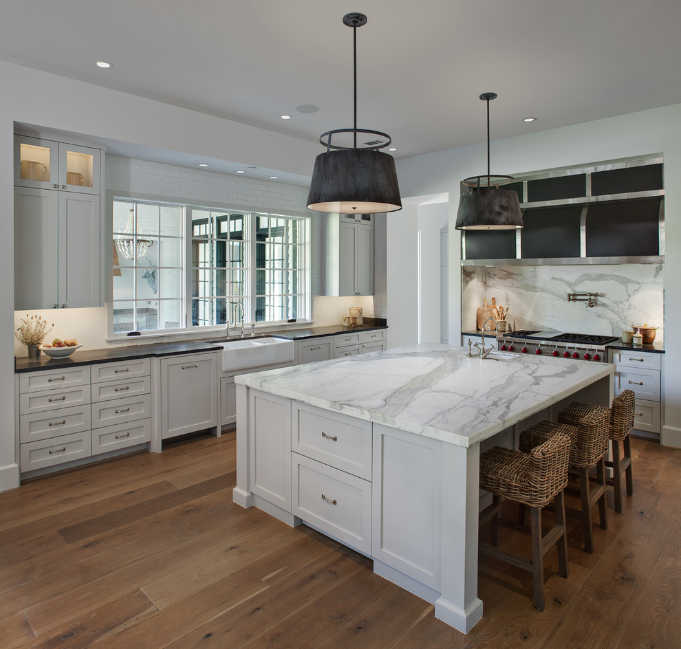 Large transitional u-shaped medium tone wood floor and brown floor enclosed kitchen photo in Houston with a farmhouse sink, shaker cabinets, white cabinets, marble countertops, white backsplash, subway tile backsplash, stainless steel appliances and an island