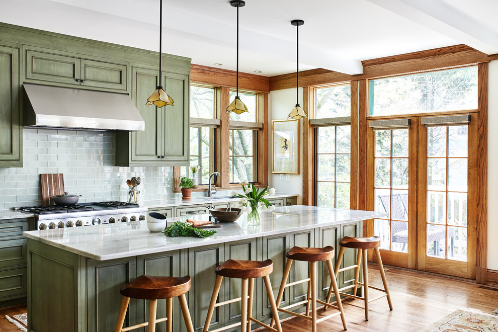 Mid-sized arts and crafts single-wall medium tone wood floor and brown floor open concept kitchen photo in DC Metro with an undermount sink, recessed-panel cabinets, green cabinets, quartz countertops, green backsplash, glass tile backsplash, paneled appliances, an island and gray countertops